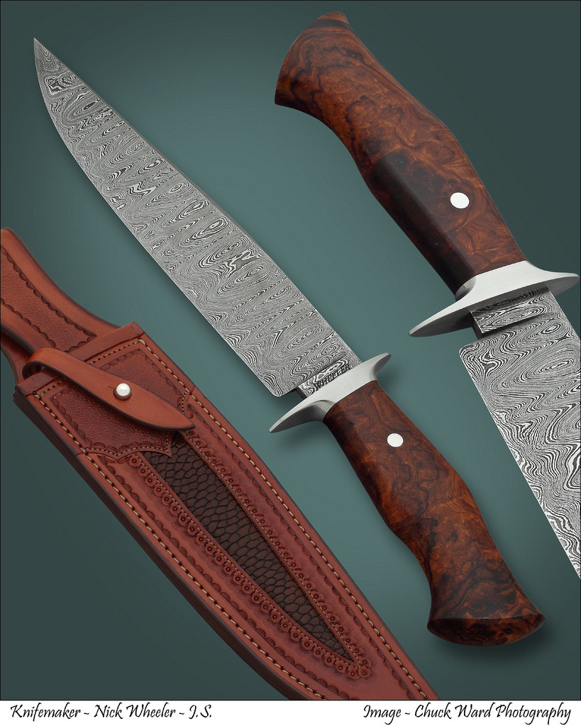 """NICK WHEELER JS, """"SAN ANTONIO DAMASCUS FIGHTER"""", 2010 -THIS BEAUTIFUL FIGHTER IS AN AGILE AND FAST AS LIGHTENING ONLY WEIGHING 10.9 OZ'S. FEATURES A PREMIUM DESERT IRONWOOD HANDLE SCUlPTURED PERFECTLY TO THE HAND. HAS NICK'S RANDOM PATTERN DAMASCUS OF 1084 AND 15N20 STEELS. THE DOUBLE FIGHTER STYLE GUARD IS SHAPED FROM 416 STAINLESS STEEL. HAS A CUSTOM PAUL LONG FANCY TOOLED SHEATH WITH A BEAVER TAIL INLAY. PURCHASED FROM NICK AT THE 2010 ABS EXPO IN SAN ANTONIO. OAL 14 1/4"""" (362MM) BL 9"""" (229MM)."""