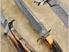 """BRUCE BUMP MS, """"ALLEN PINKERTON BOWIE"""", 2010 - A """"TAKE- DOWN"""" FIGHTER BOWIE OF BRUCE'S FEATHER PATTERN DAMASCUS FORGED FROM 1084 &15N20 STEELS. PREMINUM AMBER SAMBAR STAG FRAME CONSTRUCTED HANDLE. FINE ENGRAVING AND GOLD INLAY BY JERE DAVIDSON. 14K GOLD COIN EDGE SPACERS AND SIX 18K GOLD PINS.THE HANDLE FRAME, REAR BOLSTER AND GUARD IS 1018 STEEL COLOR CASED HARDENED BY DOUG TURNBULL AND POLISHED BY BRUCE. FEATURED ON THE FRONT INSIDE COVER OF THE WINTER 2010 ADDITION OF AMERICAN BLADESMITH JOURNAL AND """"KNIVES 2012"""" (PG.152). OAL IS 13 3/4"""" (349MM) BL 9 (229MM)."""